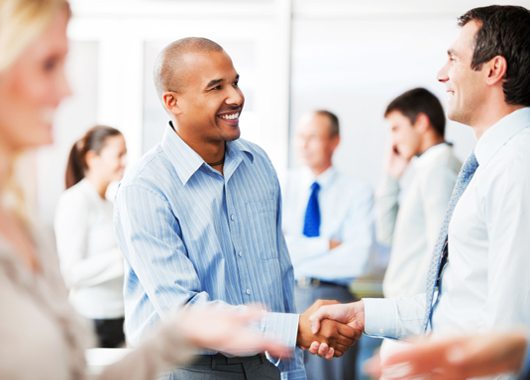 Happy business colleagues greeting each other with a handshake