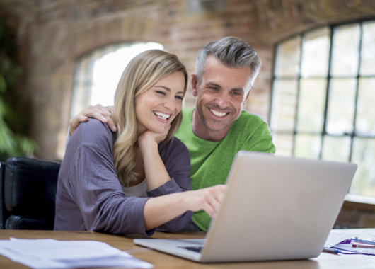 Happy online couple working on a laptop computer to refinance mortgage