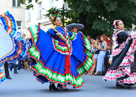 Hispanic women walking in parade.
