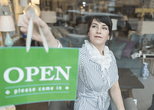 small business owner placing open sign in store window