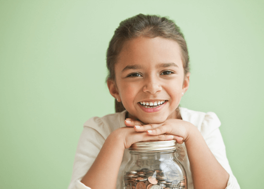 Happy girl with her jar of savings.