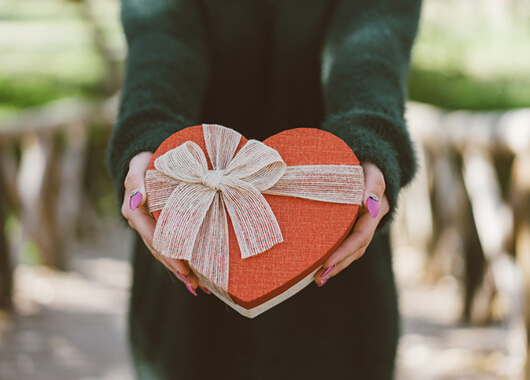 Person holding heart shaped box of chocolates