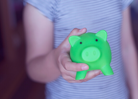 Kid holding a green piggy bank.