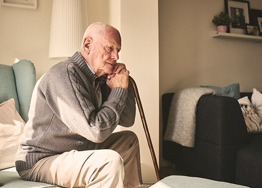 elderly man sitting in chair with cane