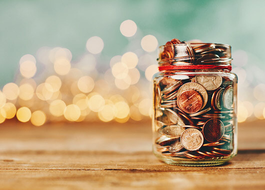 Jar of change with Christmas lights in the distance behind it.