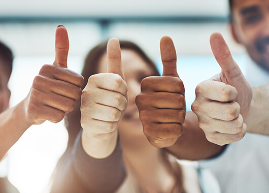 small business employees giving the thumbs up in approval of their company