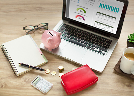 Laptop on desk with notebook, calculator, change glasses, piggy bank, and bag