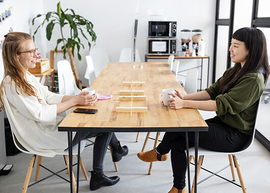 Two women sitting in conference room