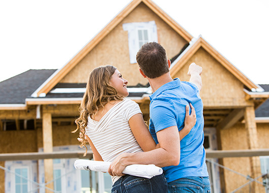 Couple in front of new home under construction